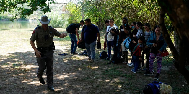 Texas Department of Public Safety officers work with a group of migrants who crossed the border and turned themselves in Del Rio, Texas.