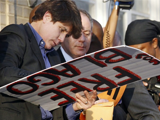 This March 14, 2012 file photo shows former Illinois Gov. Rod Blagojevich autographing a 'Free Gov. Blago' sign for one of his supporters at his home in Chicago the day before Blagojevich was due to report to prison to begin serving a 14-year sentence on corruption charges. Blagojevich's lawyers submitted an additional argument on why an appeals court in Chicago should overturn the imprisoned former governor's convictions Wednesday July, 16, 2014, in Chicago. The two-page filing with the U.S. 7th Circuit Court of Appeals refers to an April Supreme Court decision striking down laws that restrict aggregate limits on campaign contributions. (AP Photo/M. Spencer Green, File)