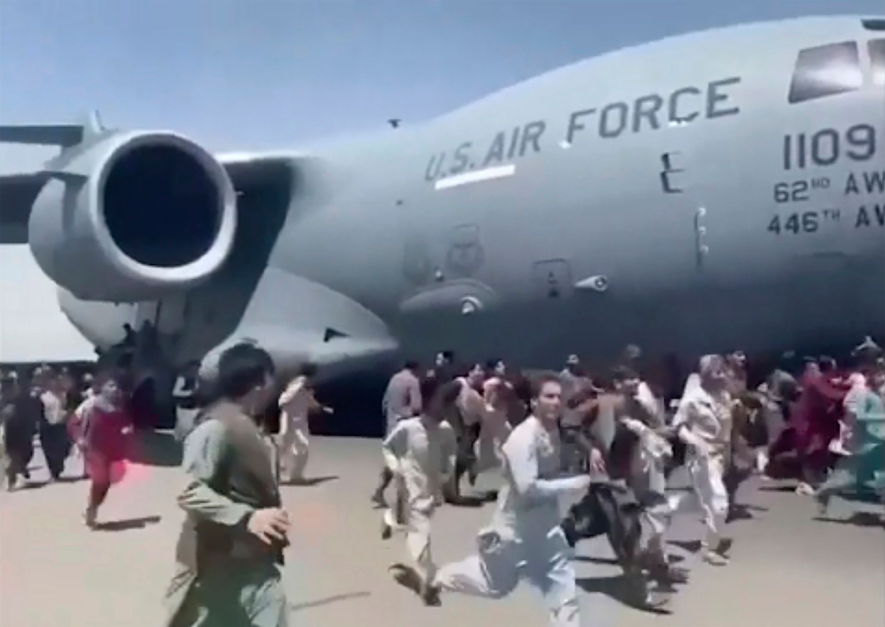 Some hundreds of people run alongside a U.S. Air Force C-17 transport plane as it moves down a runway of the international ai