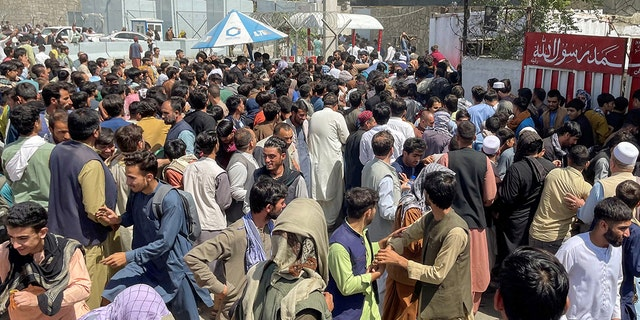 People try to get into Hamid Karzai International Airport in Kabul, Afghanistan August 16, 2021. (REUTERS/Stringer)