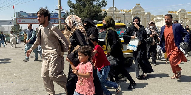 People try to get into Hamid Karzai International Airport in Kabul, Afghanistan August 16, 2021. President Biden said that nobody is being killed in Kabul despite several civilian deaths this week among those trying to escape Taliban rule. (REUTERS/Stringer)