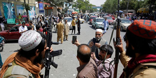 Afghans take selfie wit Taliban fighters during patrol in the city of Kabul, Afghanistan, Thursday, Aug. 19, 2021. The Taliban celebrated Afghanistan's Independence Day on Thursday by declaring they beat the United States, but challenges to their rule ranging from running a country severely short on cash and bureaucrats to potentially facing an armed opposition began to emerge. (AP Photo/Rahmat Gul)