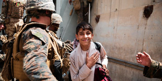 In this photo provided by the U.S. Marine Corps, a boy is processed through an Evacuee Control Checkpoint during an evacuation at Hamid Karzai International Airport, in Kabul, Afghanistan, Wednesday, Aug. 18, 2021. (Staff Sgt. Victor Mancilla/U.S. Marine Corps via AP)