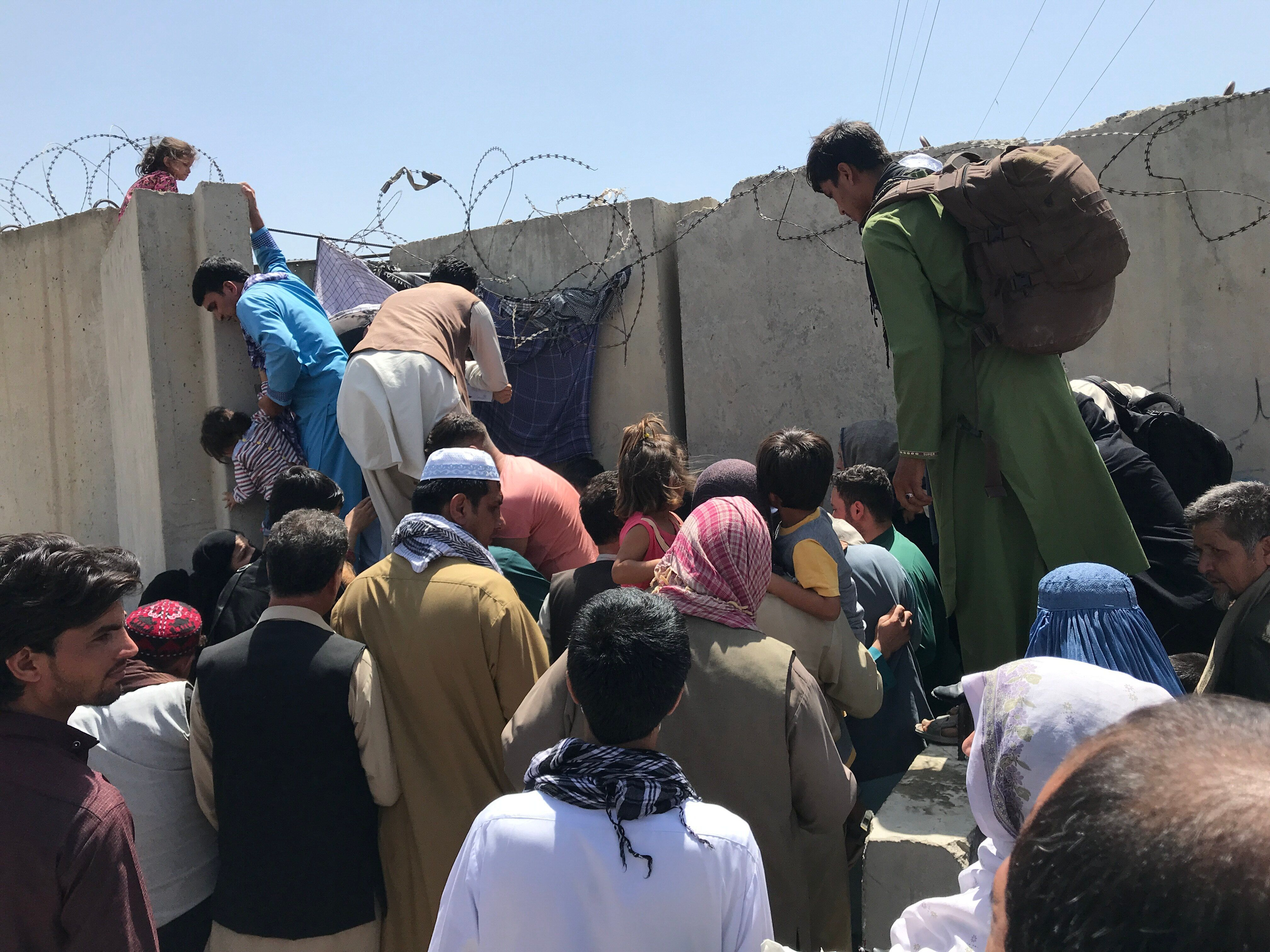 People struggle to cross the boundary wall of Kabul's Hamid Karzai International Airport on Monday to flee the country.
