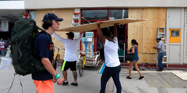Workers cover shop windows with plywood in Tulum, Quintana Roo State, Mexico, Wednesday, Aug. 18, 2021.