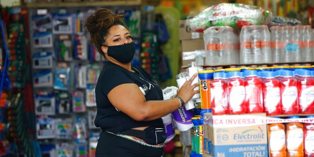 A tourist buys emergency supplies before the arrival of Hurricane Grace, in Tulum, Quintana Roo State, Mexico, Wednesday, Aug. 18, 2021.