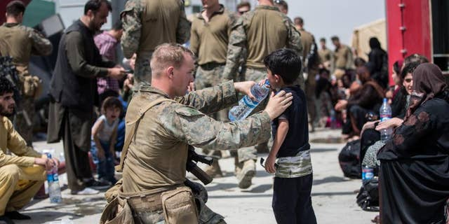 A Marine with the 24th Marine Expeditionary Unit (MEU) provides fresh water to a child during an evacuation at Hamid Karzai International Airport, Kabul, Afghanistan, Aug. 20. U.S. service members are assisting the Department of State with an orderly drawdown of designated personnel in Afghanistan. (U.S. Marine Corps photo by Sgt. Samuel Ruiz).