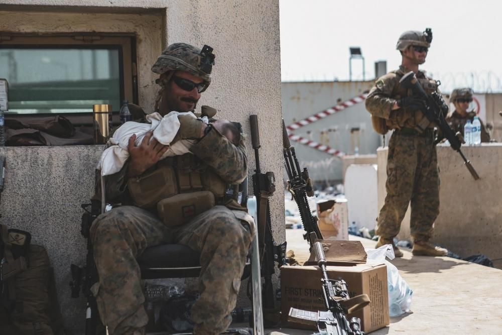 A Marine assigned to the 24th Marine Expeditionary Unit calms an infant during an evacuation at Hamid Karzai International Ai