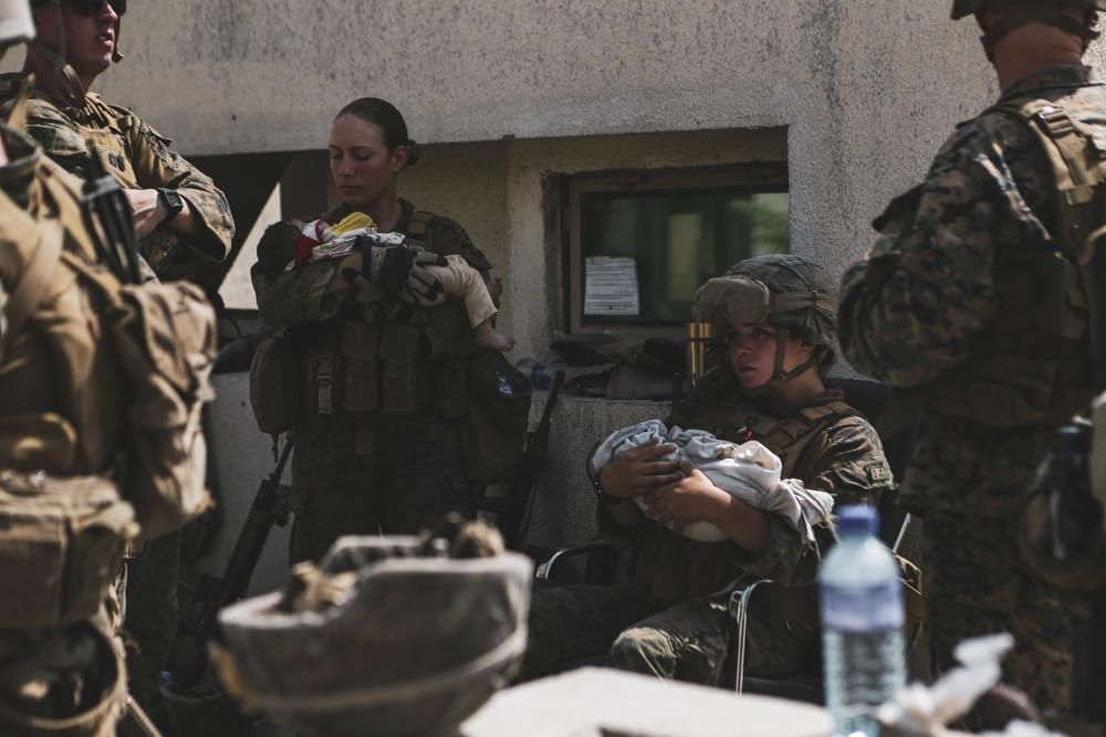 Marines assigned to the 24th Marine Expeditionary Unit calm infants during an evacuation at Hamid Karzai International Airpor