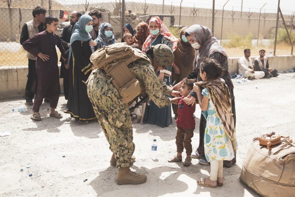 A U.S. Navy Sailor checks a child arriving at an Evacuate Control Center at Hamid Karzai International Airport, Aug. 19.