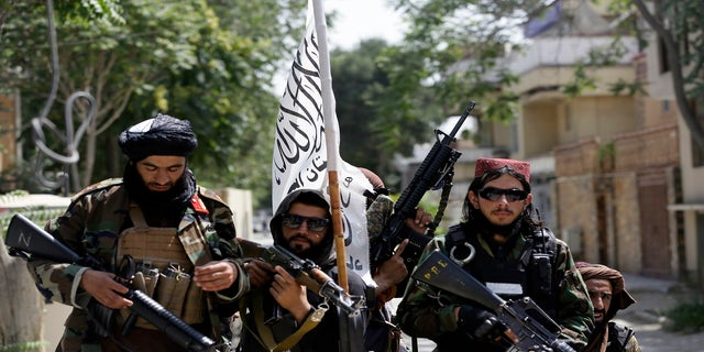 Taliban fighters display their flag on patrol in Kabul, Afghanistan, on Thursday. (AP Photo/Rahmat Gul)