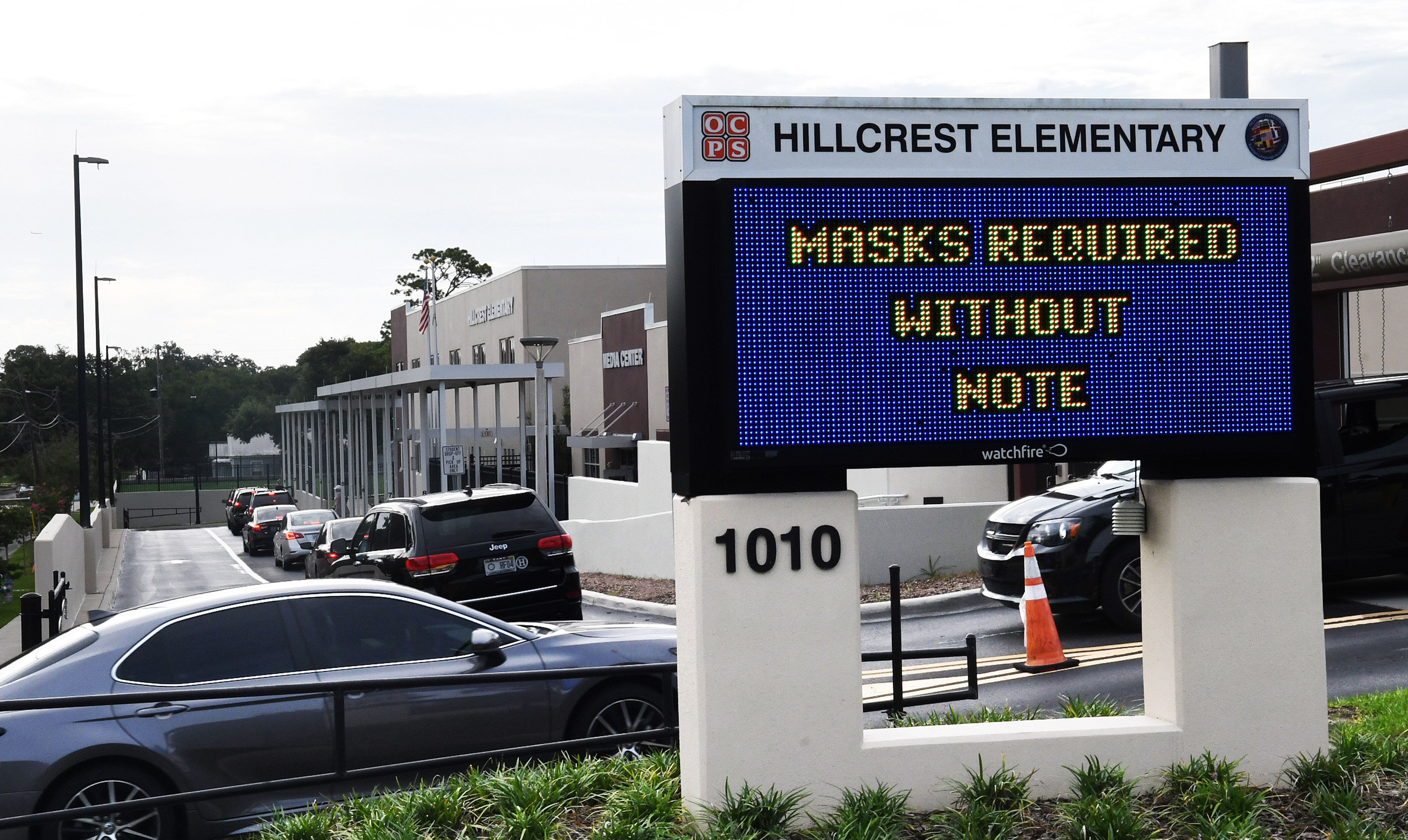 On Aug. 16, parents drop their kids off at Hillcrest Elementary school in Orlando with a sign at the entrance advising for th