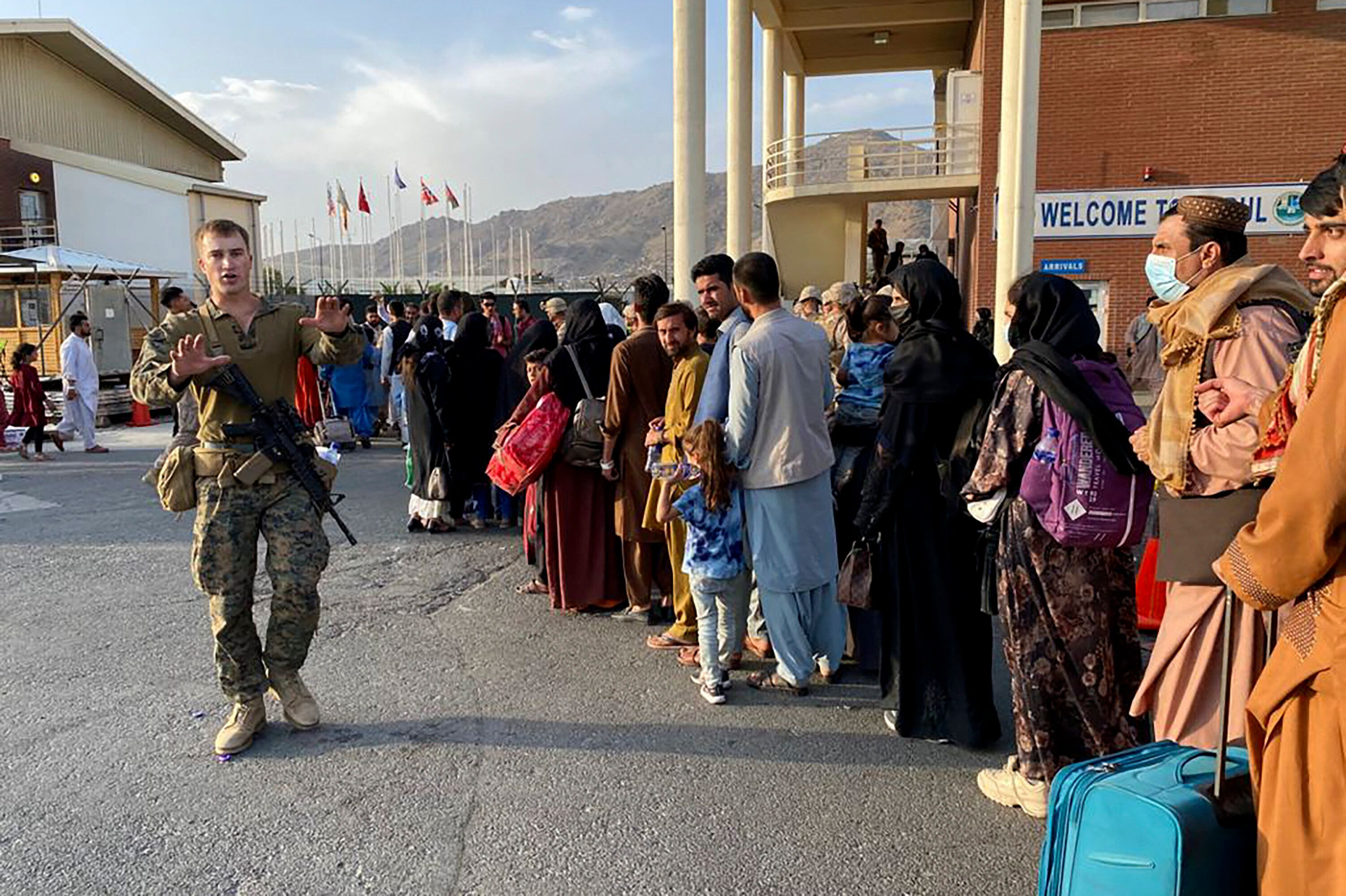 Afghan people line up to board a U.S. military aircraft to leave Afghanistan at the military airport in Kabul on Aug. 19 afte