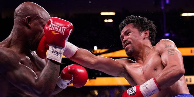 Manny Pacquiao, right, of the Philippines, hits Yordenis Ugas, of Cuba, in a welterweight championship boxing match Saturday, Aug. 21, 2021, in Las Vegas. (AP Photo/John Locher)