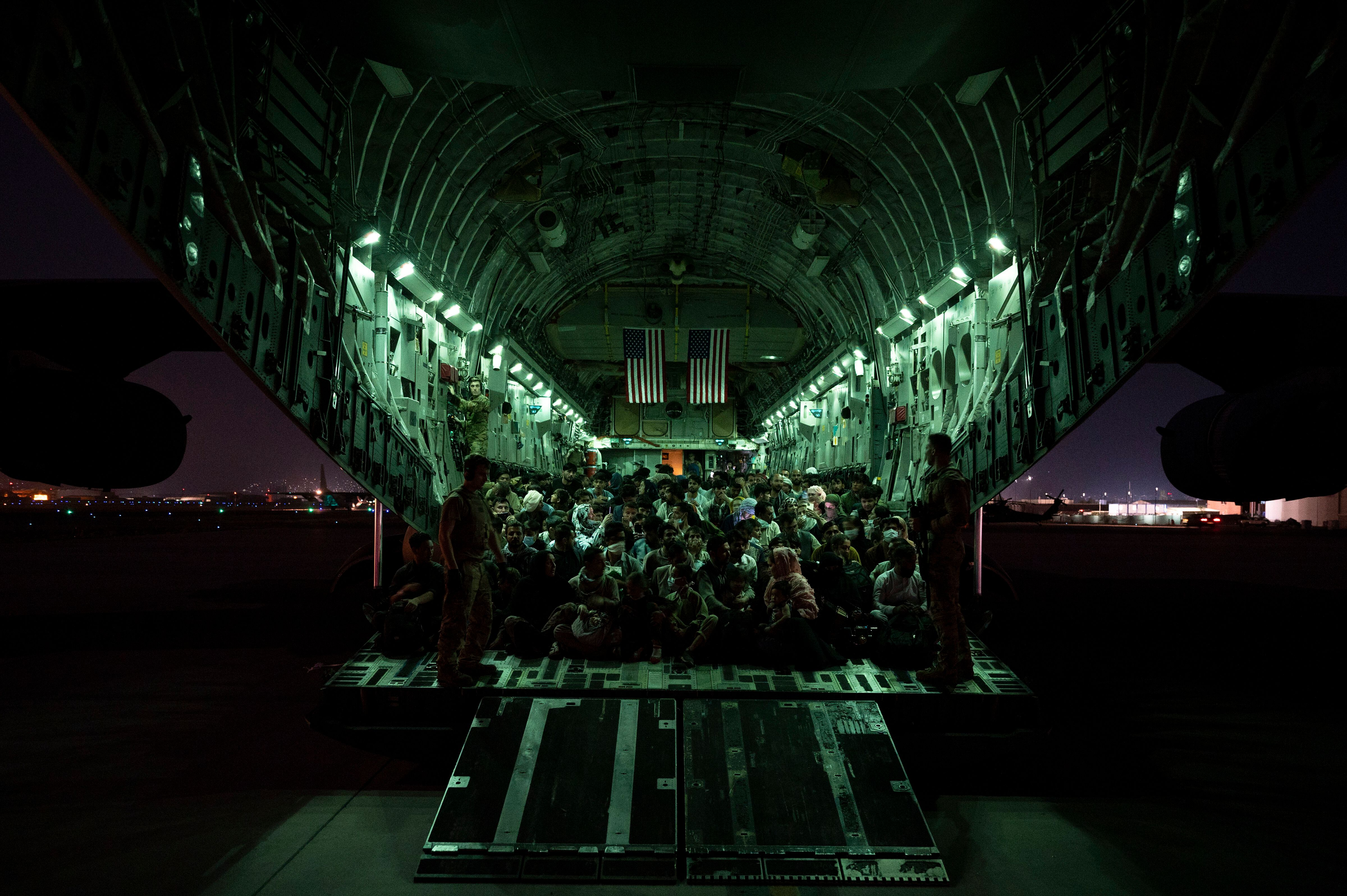 In this handout provided by the U.S. Air Force, refugees are seen aboard a C-17 Globemaster III on Aug. 21. in Kabul. Thousan