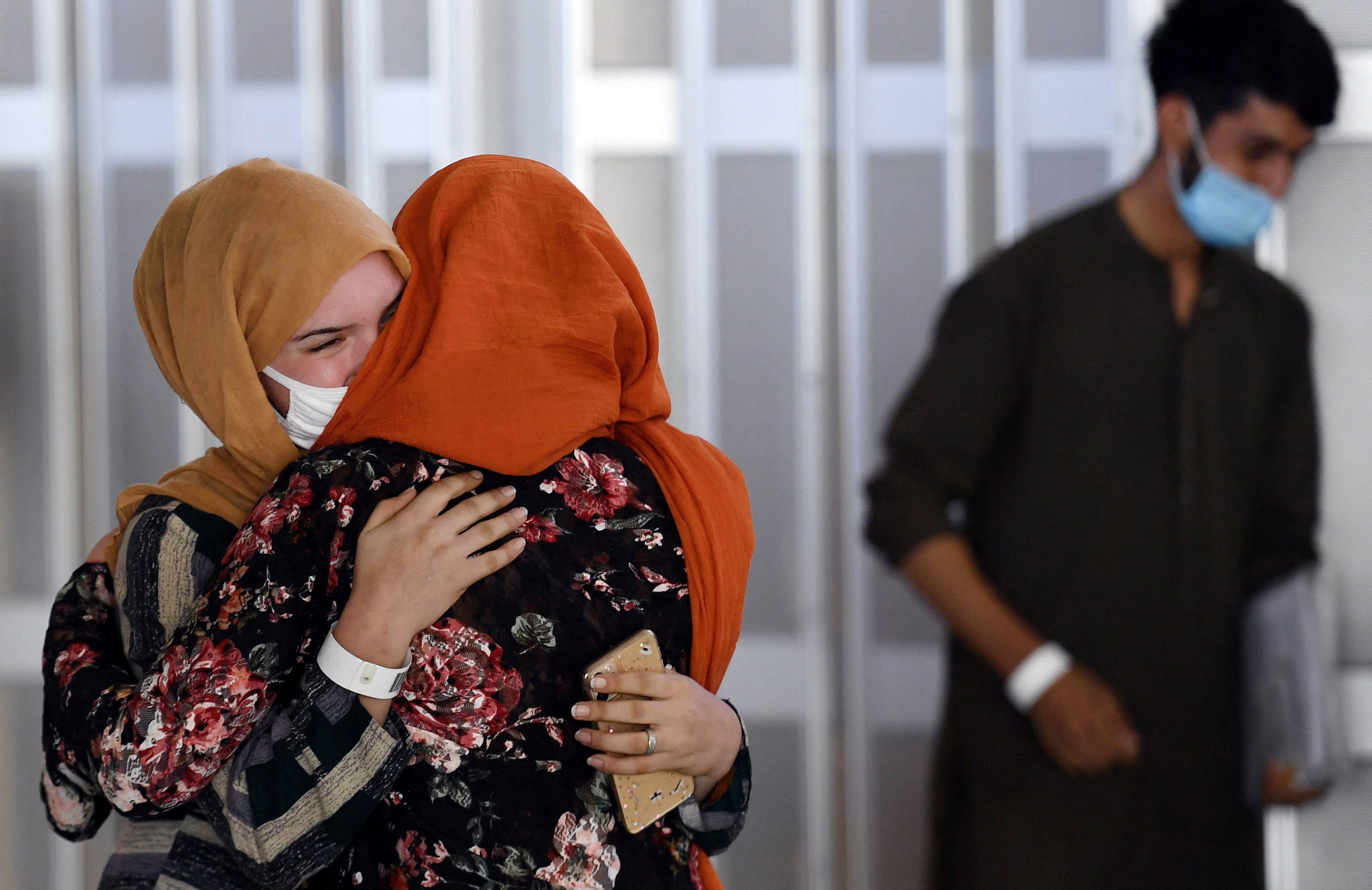 A woman embraces her sister-in-law (L) as she arrives with other Afghan refugees at Dulles International Airport on Aug. 23.