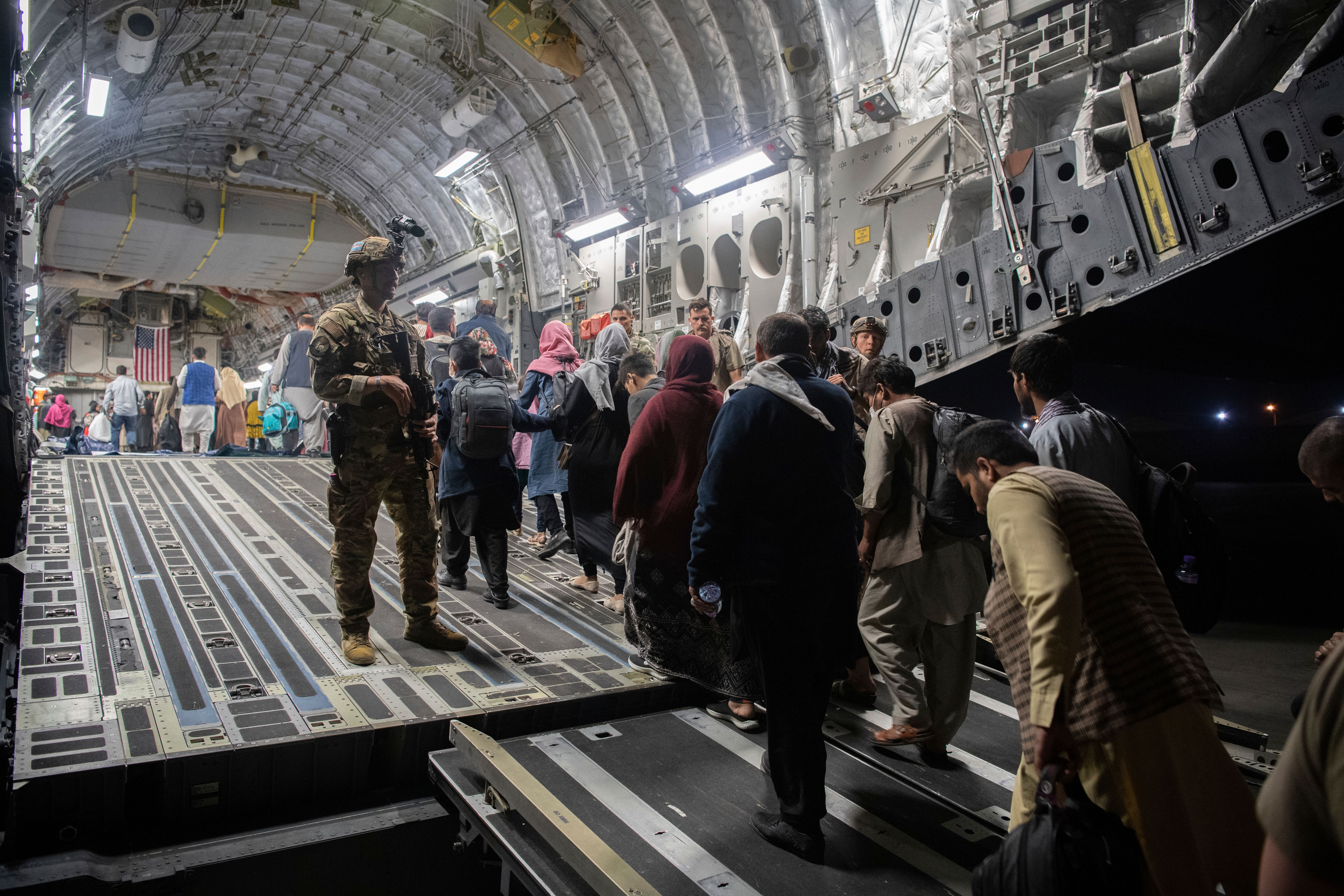 In this Aug. 22, 2021, photo provided by the U.S. Air Force, Afghan passengers board a U.S. Air Force C-17 Globemaster III du
