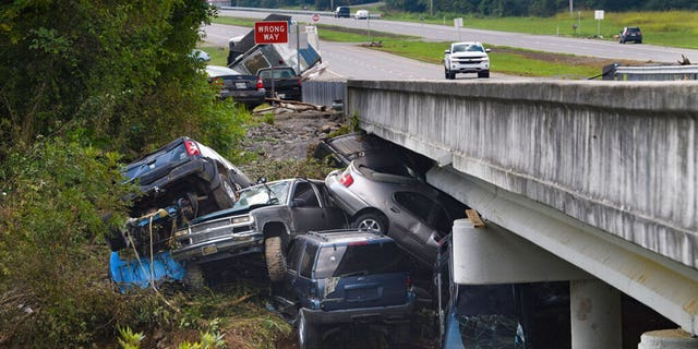 Cars are stacked on top of each other on the banks of Blue Creek being swept up in flood water, Monday, Aug. 23, 2021, in Waverly, Tenn. Heavy rains caused flooding in Middle Tennessee days ago and have resulted in multiple deaths as homes and rural roads were washed away.