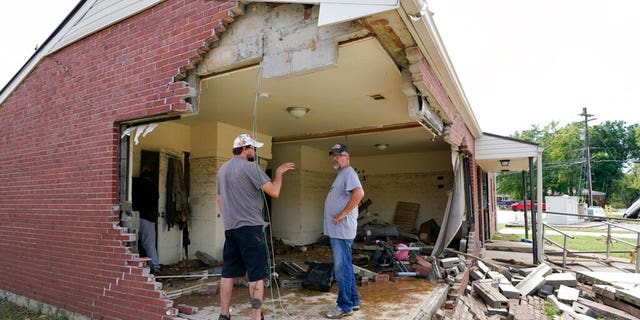 Brian Mitchell, right, looks through the damaged home of his mother-in-law along with family friend Chris Hoover, left, Sunday, Aug. 22, 2021, in Waverly, Tenn. Heavy rains caused flooding Saturday in Middle Tennessee and have resulted in multiple deaths as homes and rural roads were washed away.