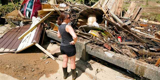 A woman looks at debris washed up against a bridge over a stream Sunday, Aug. 22, 2021, in Waverly, Tenn. Heavy rains caused flooding Saturday in Middle Tennessee and have resulted in multiple deaths as homes and rural roads were washed away.