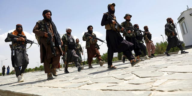 In this Aug. 19, 2021, file photo, Taliban fighters patrol in Kabul, Afghanistan. After the Taliban takeover, employees of the collapsed government, civil society activists and women are among the at-risk Afghans who have gone into hiding or are staying off the streets. (AP Photo/Rahmat Gul, File)