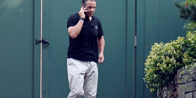 Gov. Andrew Cuomo talks on the phone while walking with his dog Captain at the New York state Executive Mansion, Saturday, Aug. 7, 2021, in Albany, N.Y.