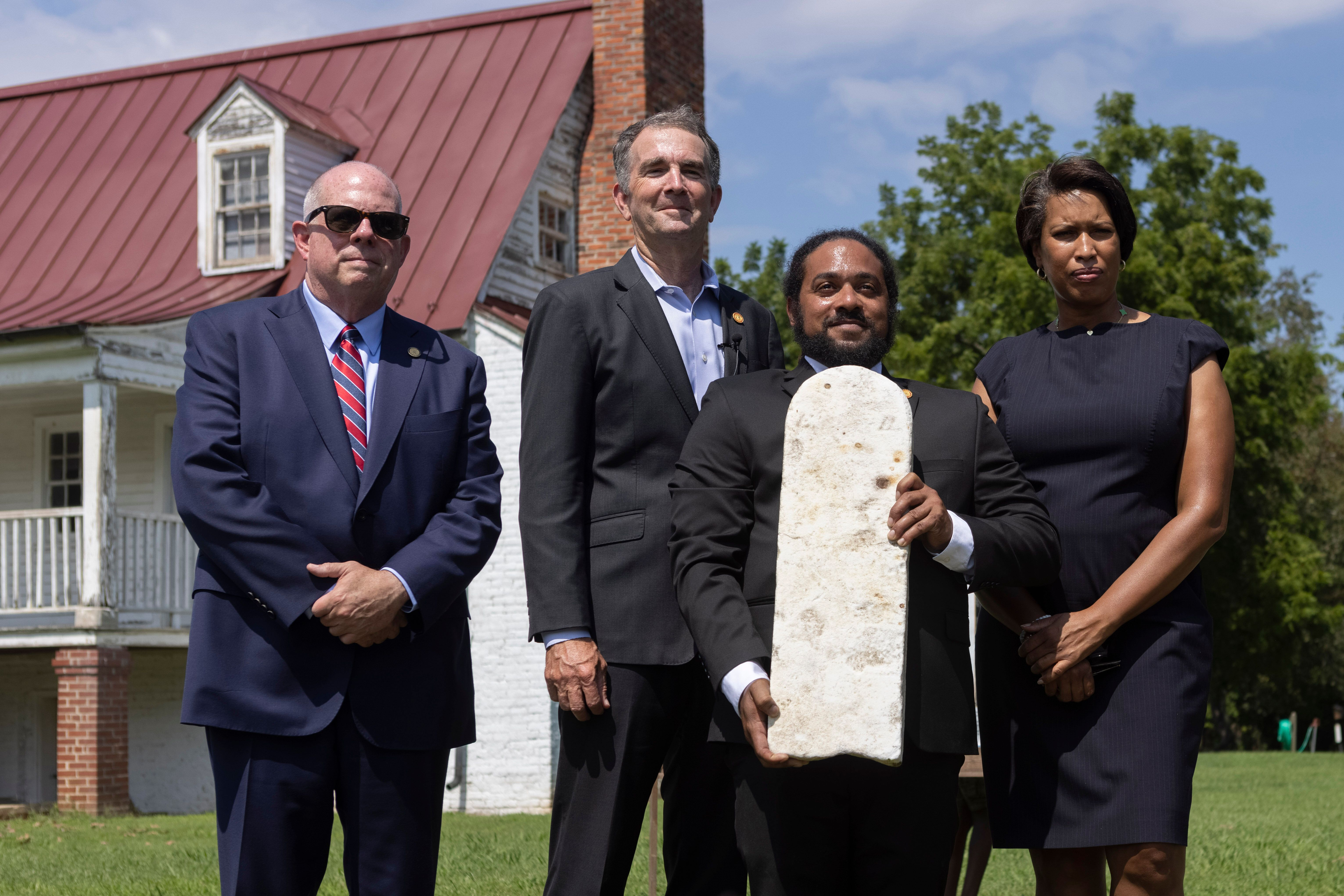 Nathan Burrell, with the Virginia Department of Conservation and Recreation, holds a grave marker and poses with, from left,