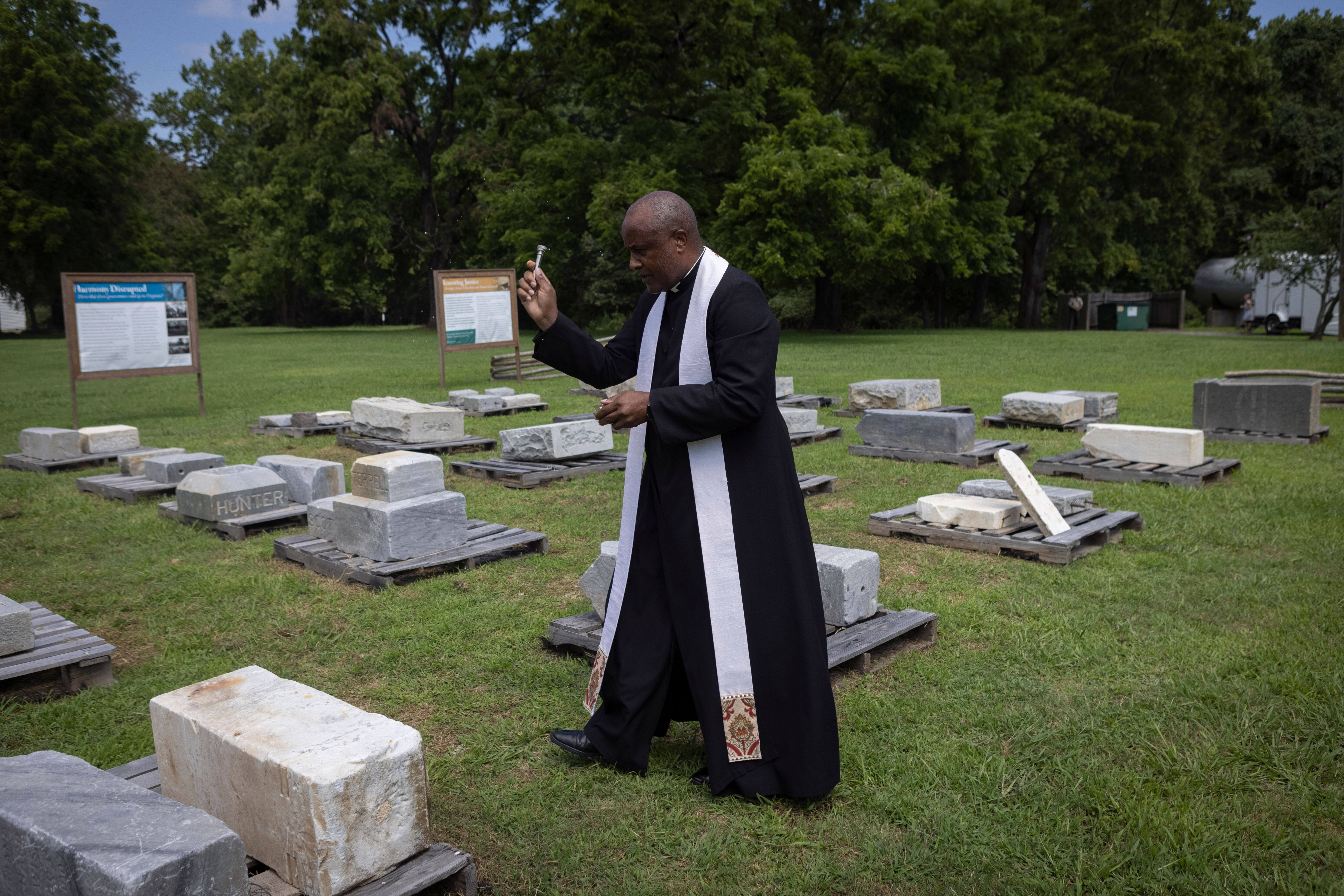 Rev. Lee Gandiya of St. Pauls Episcopal Church blesses gravestones during a ceremonial transfer on Monday at Caledon State Pa