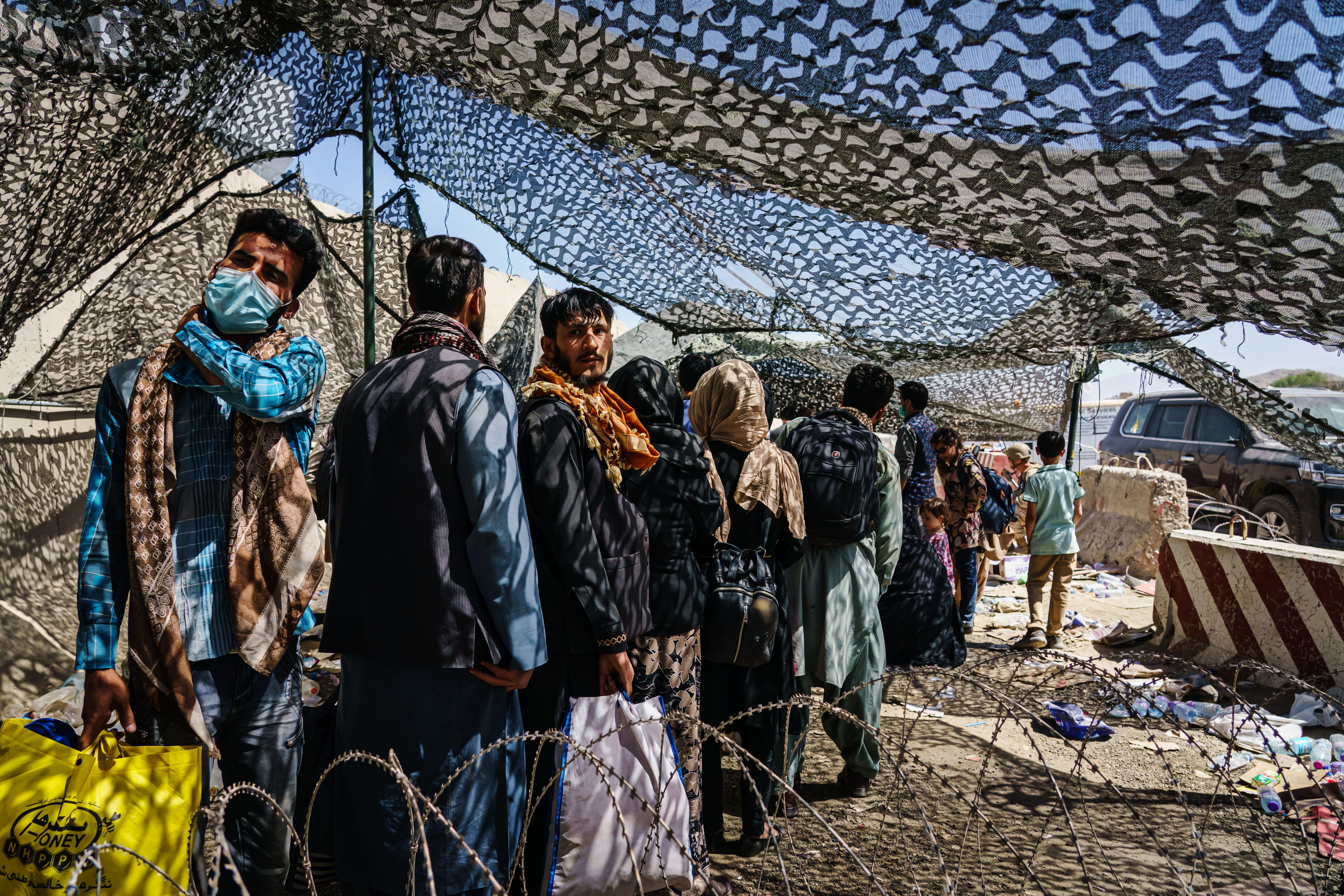 Afghan refugees leave a processing line before moving to a waiting area for a flight out of Kabul, Afghanistan, on Aug. 25.