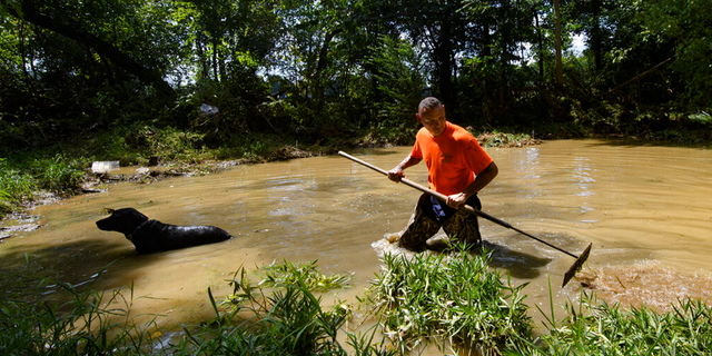 Dustin Shadownes, of Ashland City Fire Department, searches a creek for missing persons along with a cadaver dog, Monday, Aug. 23, 2021, in Waverly, Tenn.