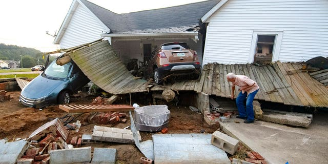 Ernest Hollis looks for items at his granddaughter's house that was devastated by floodwaters, Monday, Aug. 23, 2021, in Waverly, Tenn.