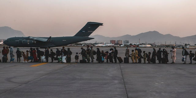 In this image provided by the U.S. Marine Corps, evacuees wait to board a Boeing C-17 Globemaster III, at Hamid Karzai International Airport, Kabul, Afghanistan, on Monday. (AP/Sgt. Isaiah Campbell/U.S. Marine Corps)