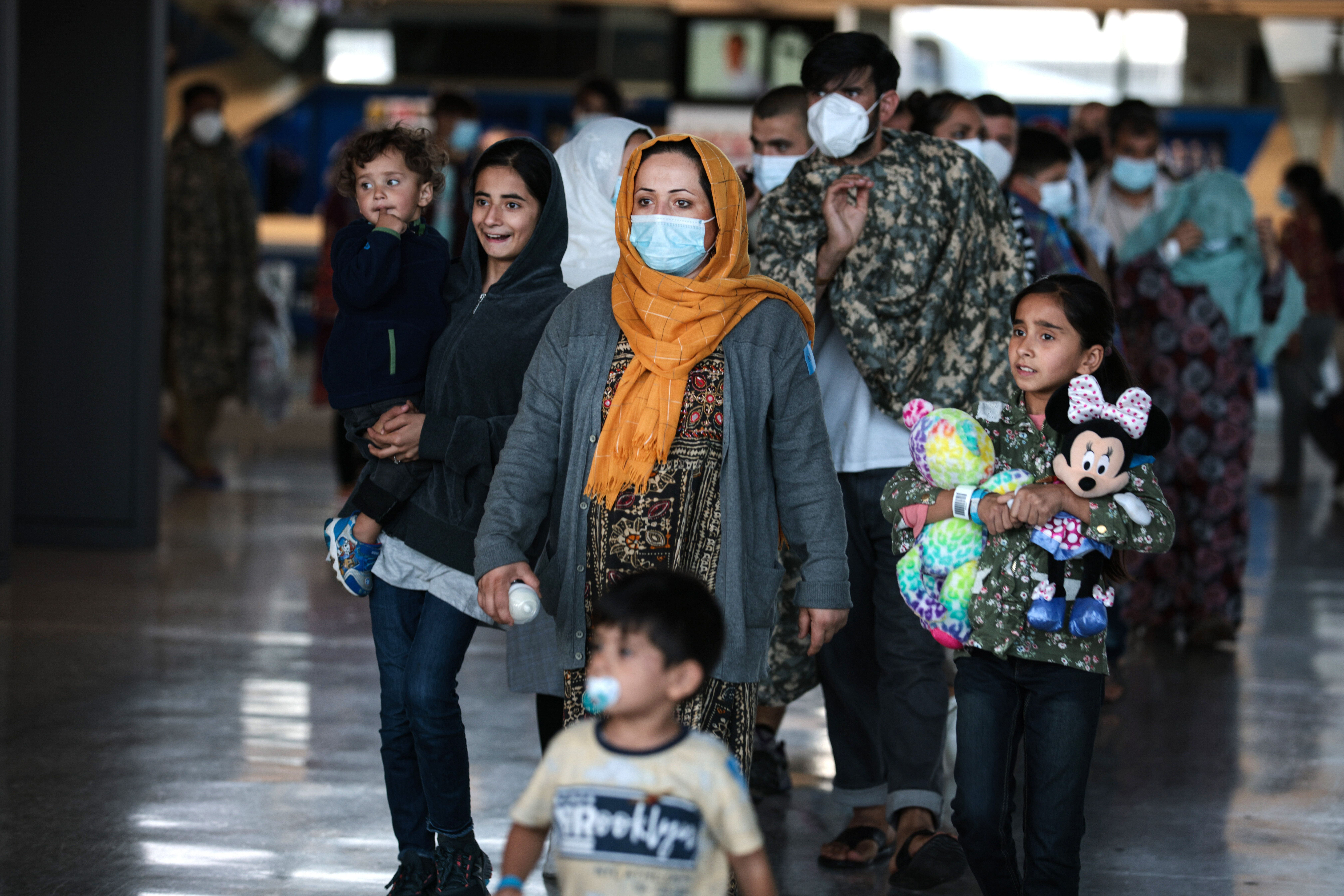 A family of people evacuated from Afghanistan are led through the arrival terminal at the Dulles International Airport to boa