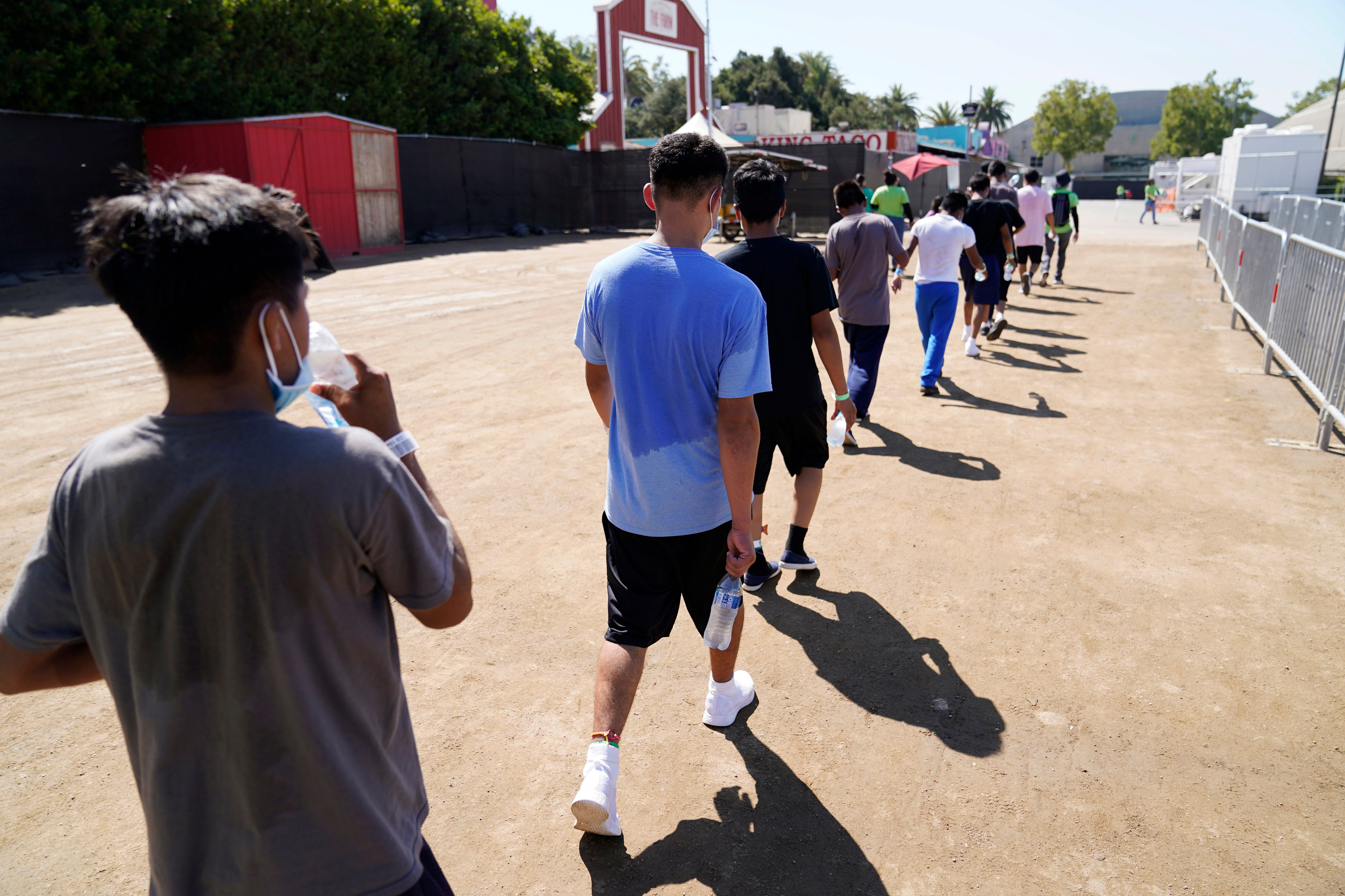 In this July 2, 2021, file photo, children walk together after a game of soccer at an emergency shelter for migrant children