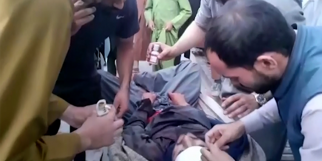 In this frame grab from video, people attend to a wounded man near the site of a deadly explosion outside the airport in Kabul, Afghanistan, Thursday, Aug. 26, 2021. Two suicide bombers and gunmen have targeted crowds massing near the Kabul airport, in the waning days of a massive airlift that has drawn thousands of people seeking to flee the Taliban takeover of Afghanistan.