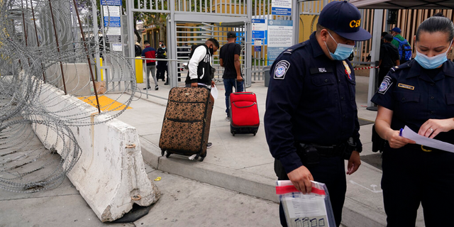 FILE: Honduran Alex Cortillo, left, and his stepbrother pull their suitcases to the border crossing into the U.S. to begin the asylum process, in Tijuana, Mexico.