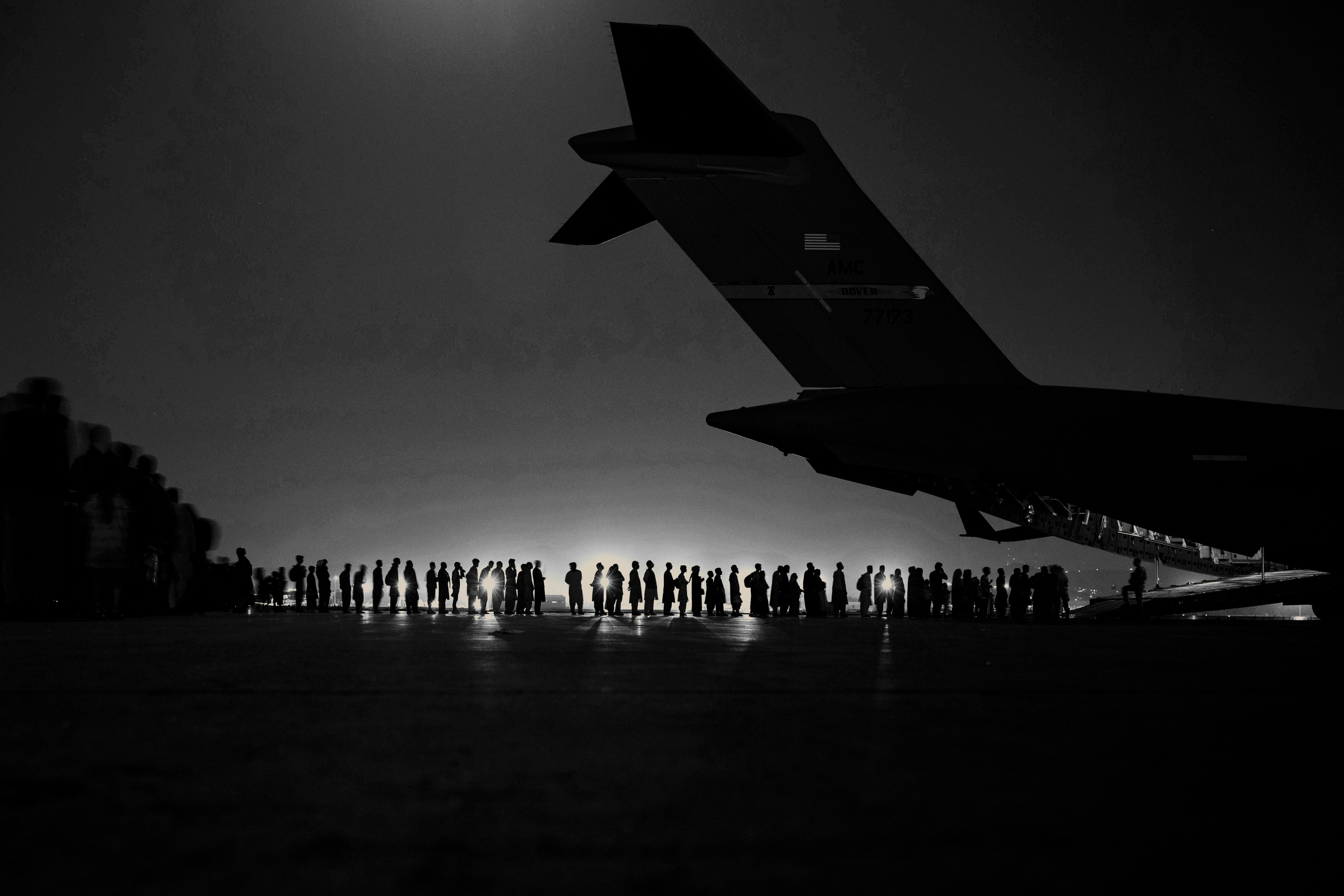 A U.S. Air Force aircrew, assigned to the 816th Expeditionary Airlift Squadron, prepare to load qualified evacuees aboard a U