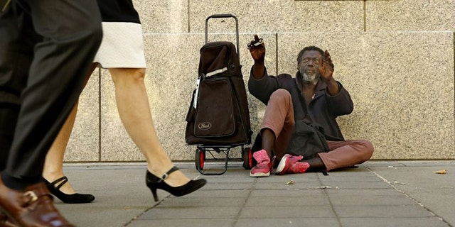 Carl Wallace, who says he is homeless and lives on the streets, waves to people passing by in Sacramento, Calif., Wednesday, June 26, 2019. New government data, released Wednesday show the number of people experiencing homelessness in Sacramento County has increased 19% over the last two years. (AP Photo/Rich Pedroncelli)