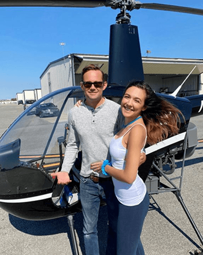 This undated photo provided by John Pilkington shows helicopter pilot Joel Boyers and his fiancée, Melody Among at John C. Tune airport in Nashville, Tenn. The two helped rescue people from rooftops during a devastating flash flood that killed 20 people in Waverly, Tennessee, on Saturday, Aug. 21, 2021. (John Pilkington via AP)