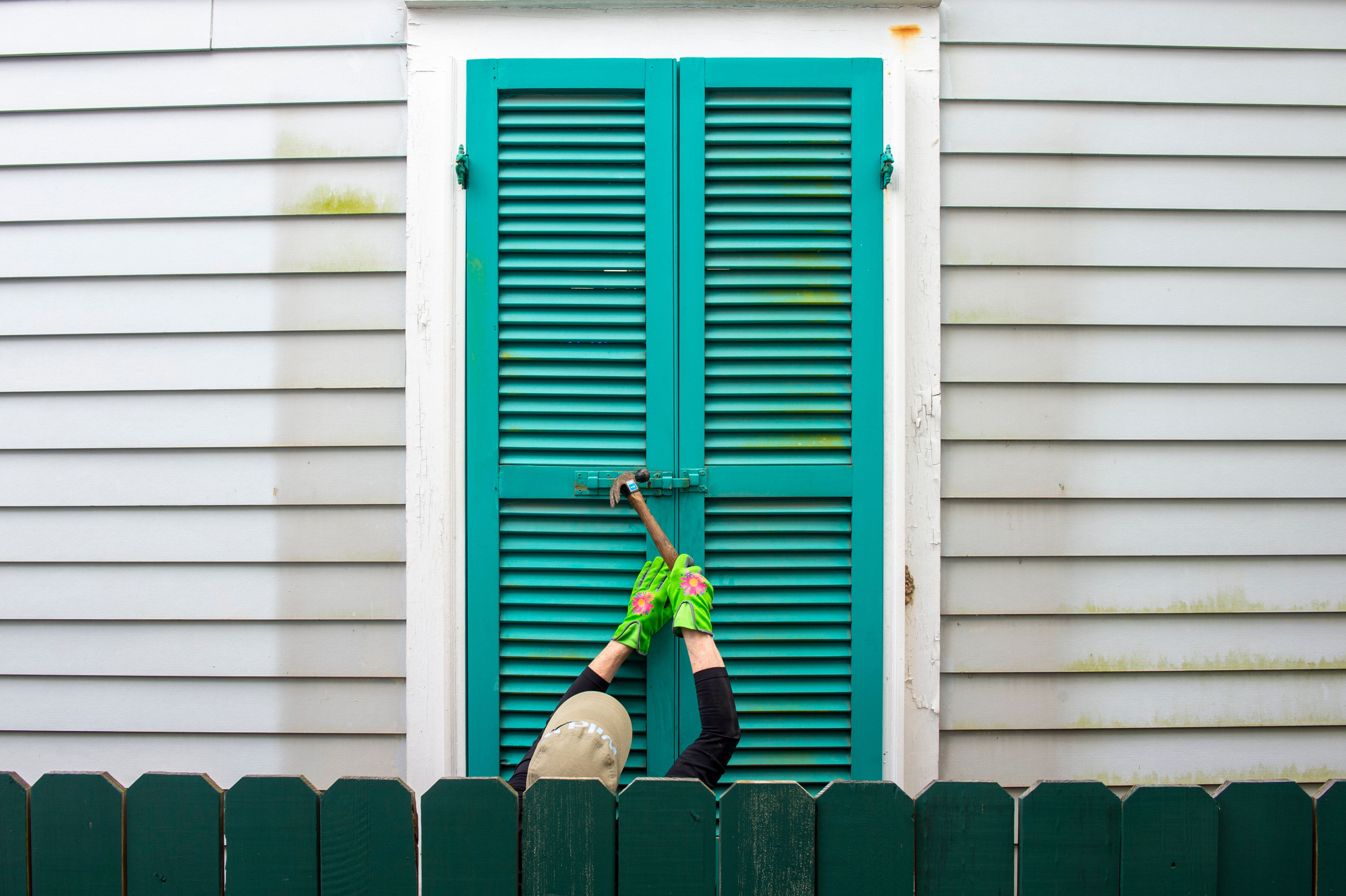 Storm shutters are hammered closed on a 100-year-old house, Friday, August 27, 2021, in New Orleans, as residents prepare for