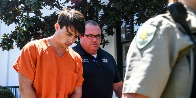 """Brandon Theesfeld, left, is led from the Lafayette County Courthouse in Oxford, Miss., Tuesday, July 23, 2019, after being arraigned in connection with the death of 21-year-old University of Mississippi student Alexandria """"Ally"""" Kostial. (Bruce Newman/The Oxford Eagle via AP)"""