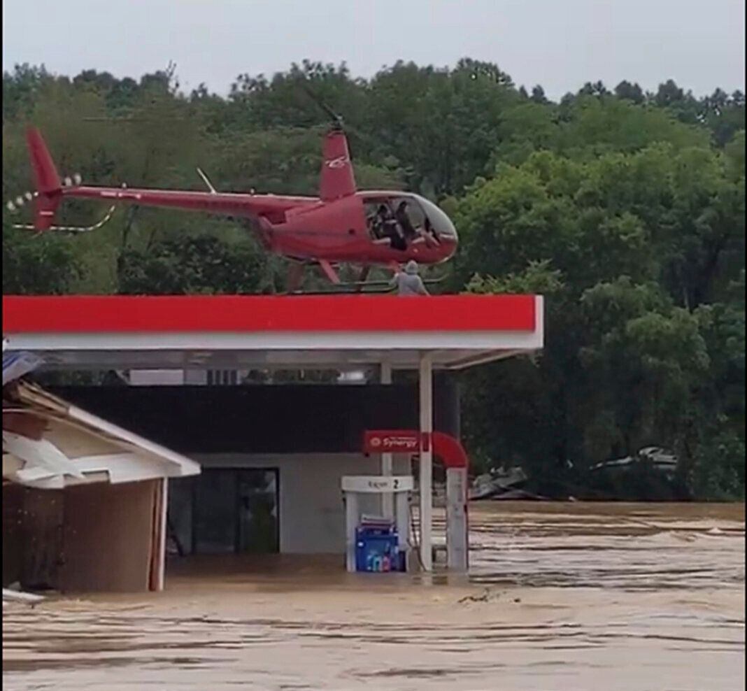 This image from video provided by Jeani Rice-Cranford shows Nashville-based helicopter pilot Joel Boyers rescuing people from