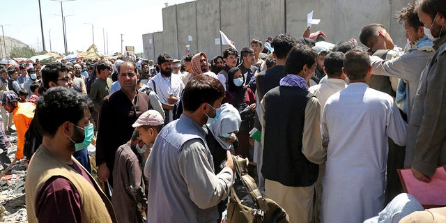 Hundreds of people, some holding documents, gather near an evacuation control checkpoint on the perimeter of the Hamid Karzai International Airport, in Kabul, Afghanistan, Thursday, Aug. 26, 2021.