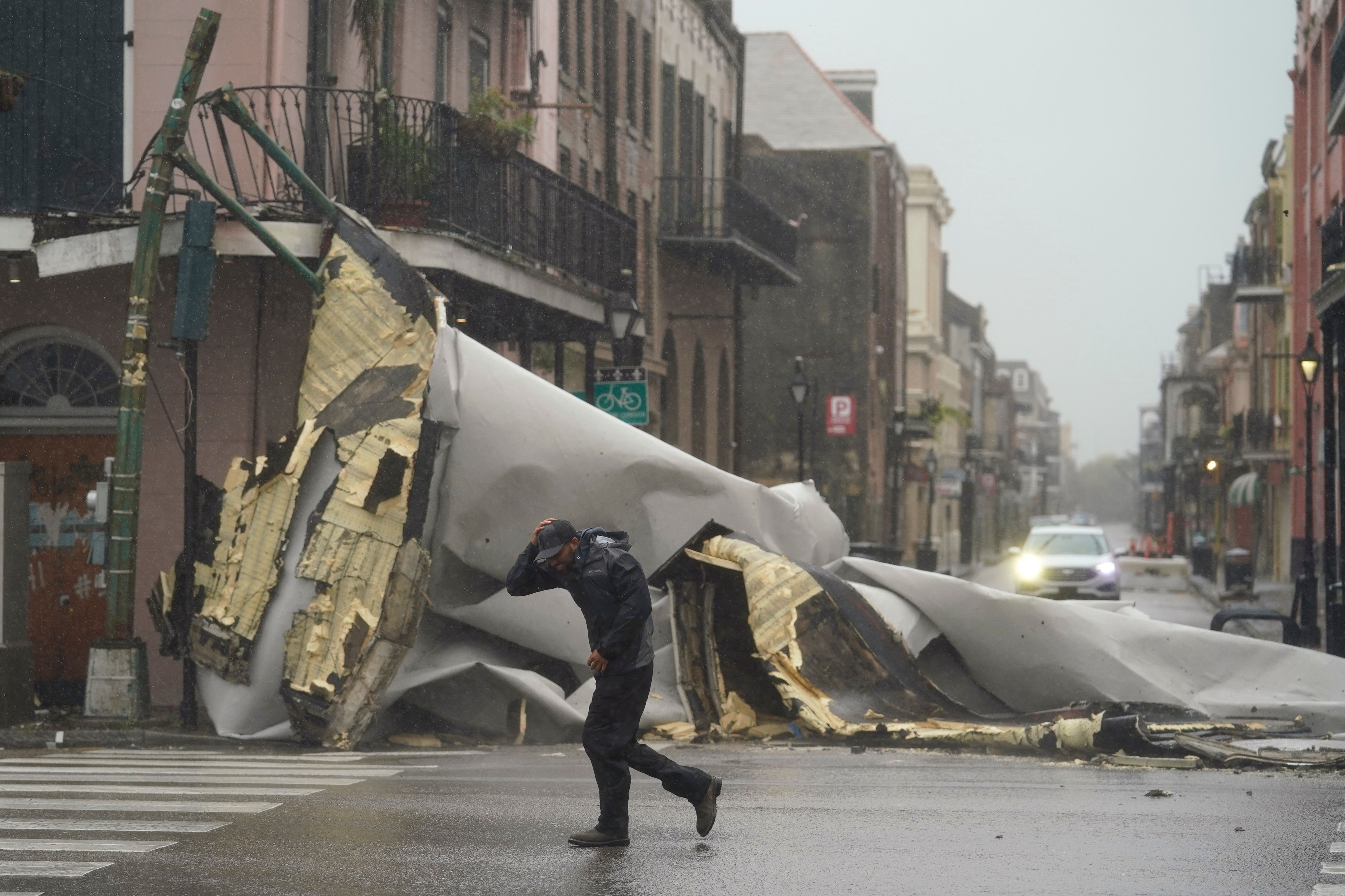 A man passes by a section of roof that was blown off of a building in the French Quarter by Hurricane Ida winds in New Orlean