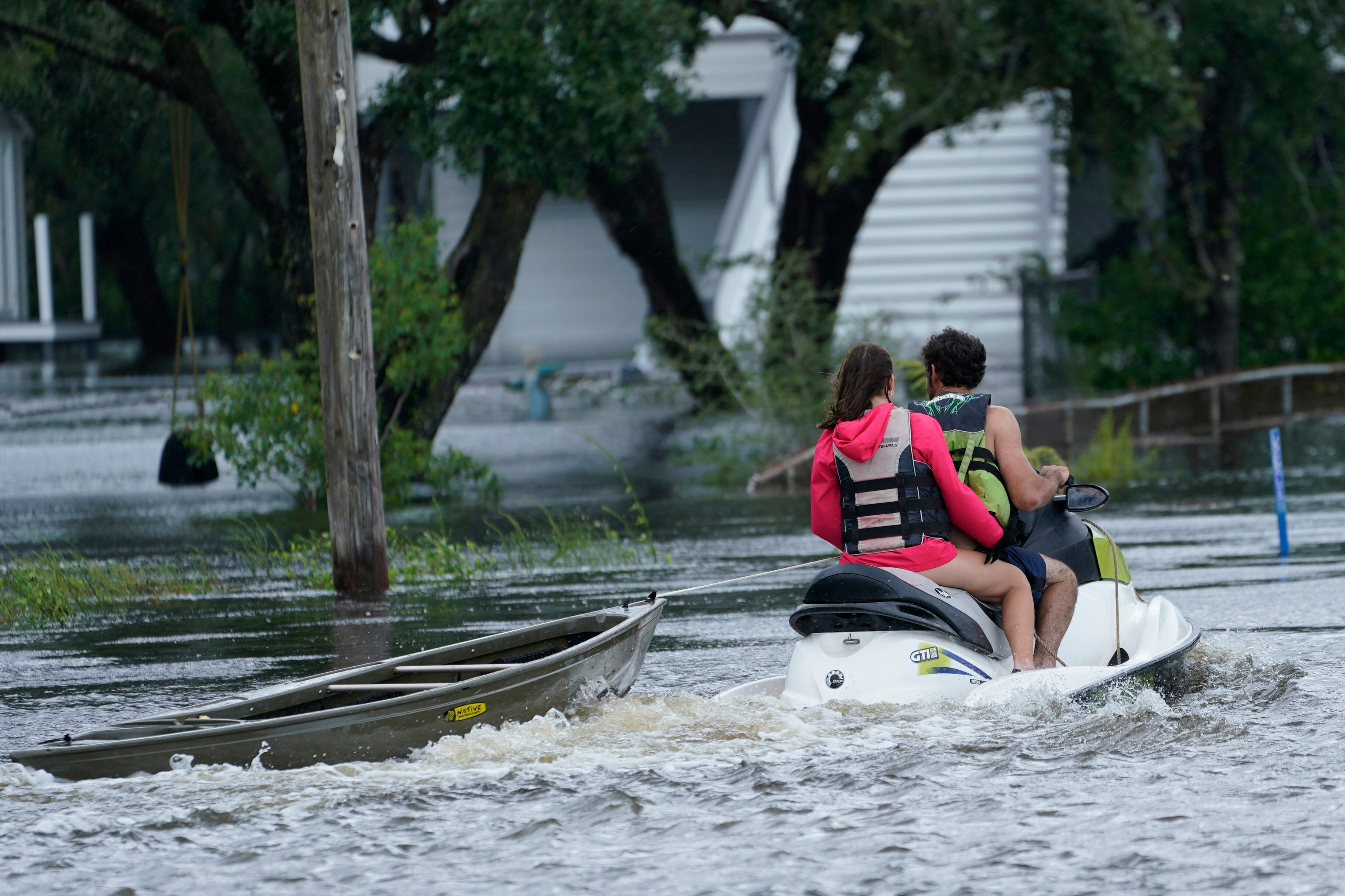 A local resident on a jet ski tows a canoe to a flooded house as outer bands of Hurricane Ida arrive on Sunday in Bay Saint L