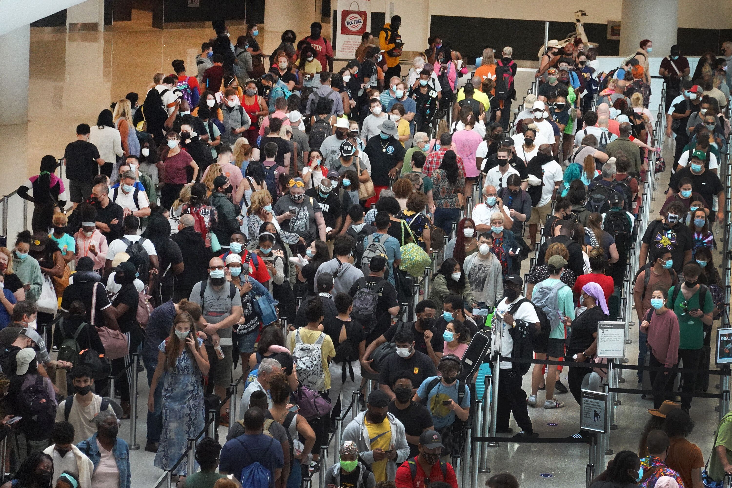 People stand in line to get through the TSA security checkpoint at Louis Armstrong New Orleans International Airport on Satur