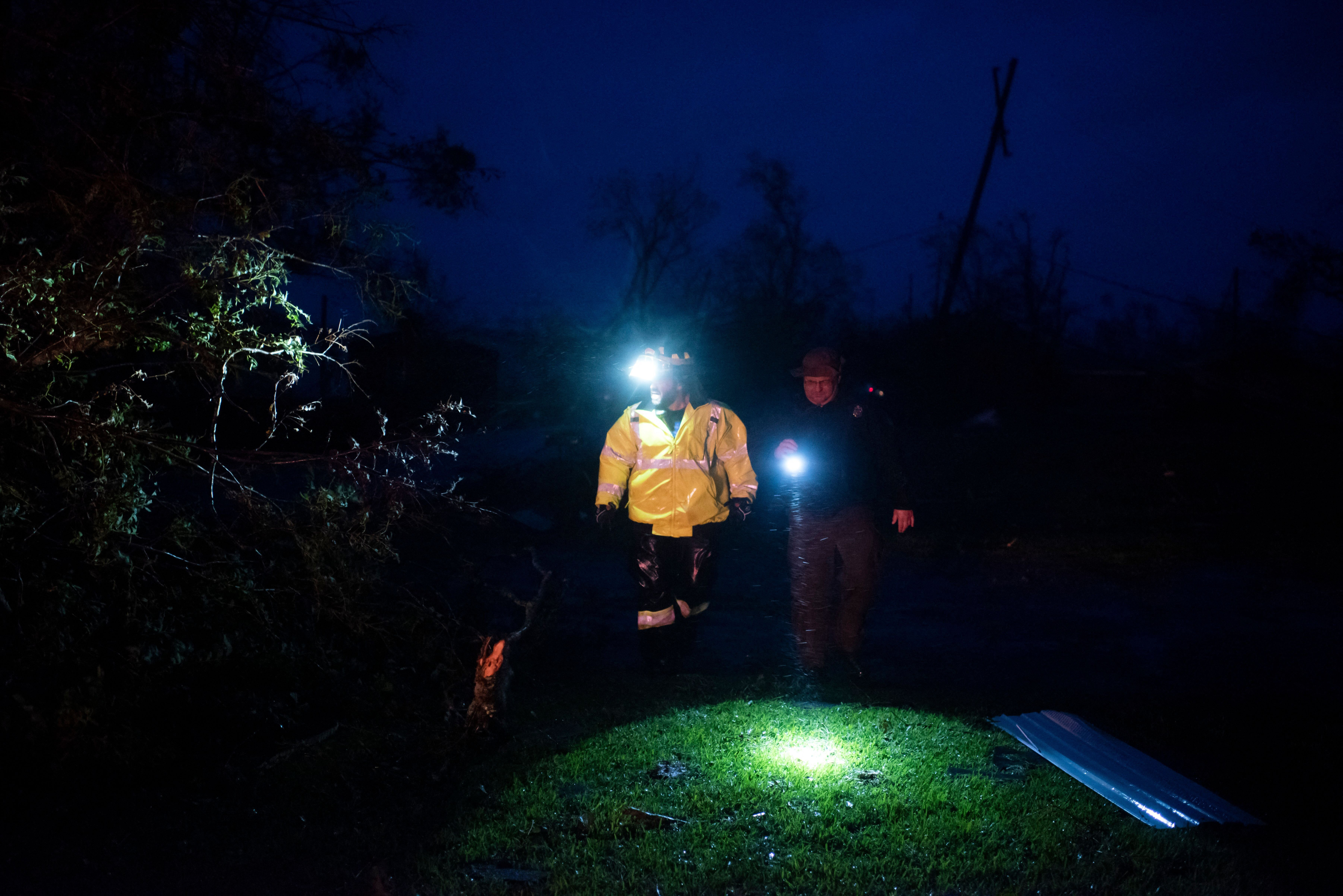 Montegut and Bourg firefighters cut through trees on the road in Bourg, Louisiana as Hurricane Ida passes on August 29, 2021.