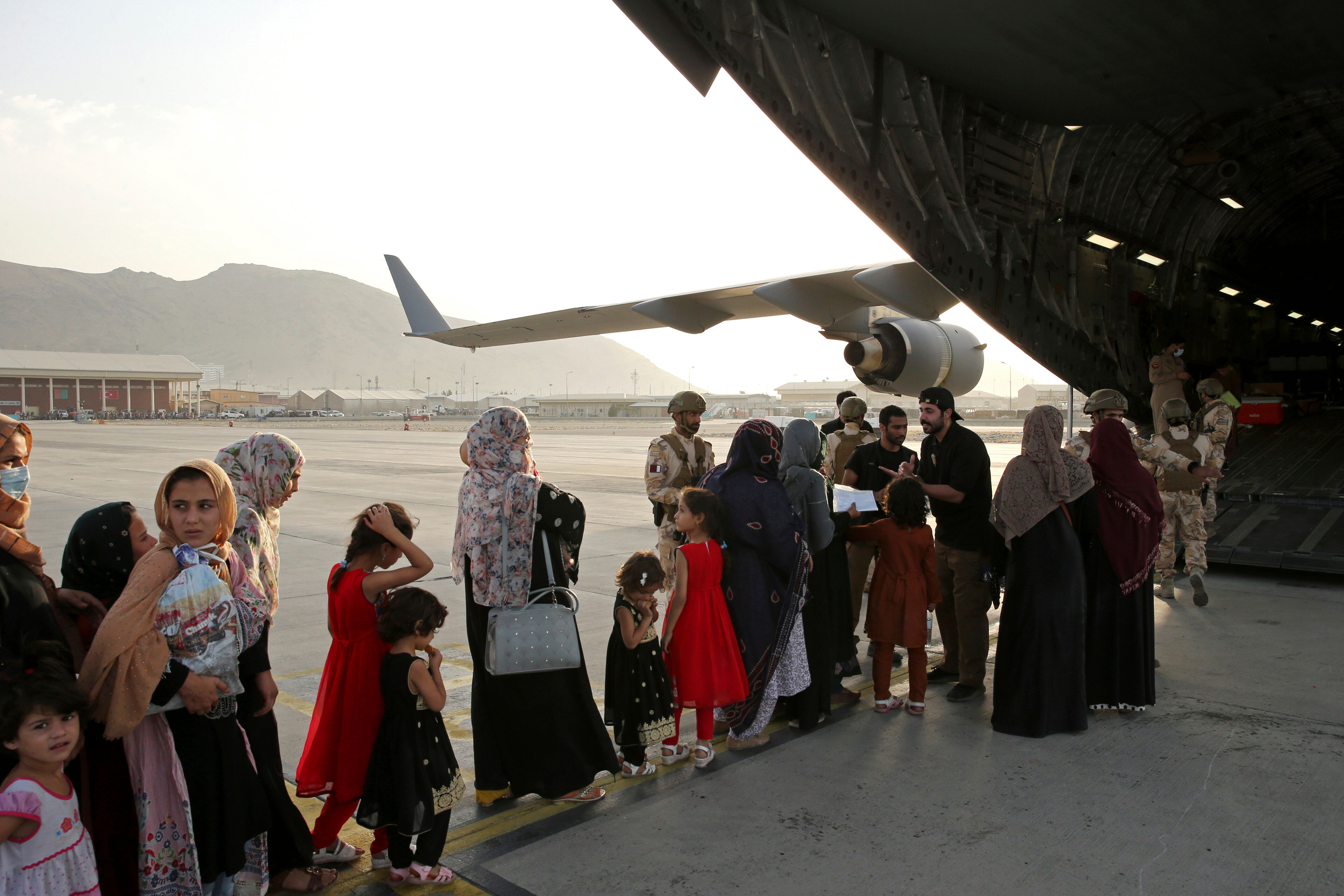 Afghans prepare to to be evacuated aboard a Qatari transport plane, at Hamid Karzai International Airport in Kabul, Afghanist