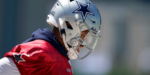 Dallas Cowboys quarterback Dak Prescott jogs onto the practice field for a workout at the team's NFL football training facility in Frisco, Texas, Wednesday, Aug. 25, 2021. (AP Photo/Tony Gutierrez)