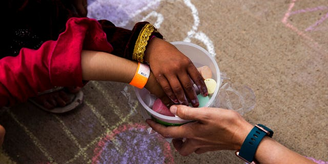 In this Aug. 31 , 2021, photo provided by the U.S. Army, Afghan children take a piece of chalk at a children's activity event held by non-governmental charities at Fort McCoy in Wisconsin. (Spc. Rhianna Ballenger/U.S. Army via AP)